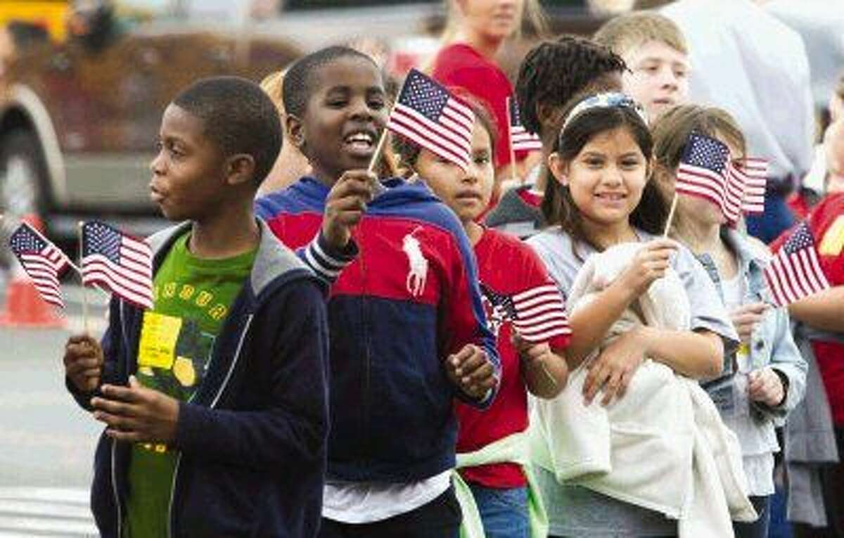 Rice Elementary students wave flags as they wait to enter Moorhead Stadium for a Veterans Day celebration Wednesday.