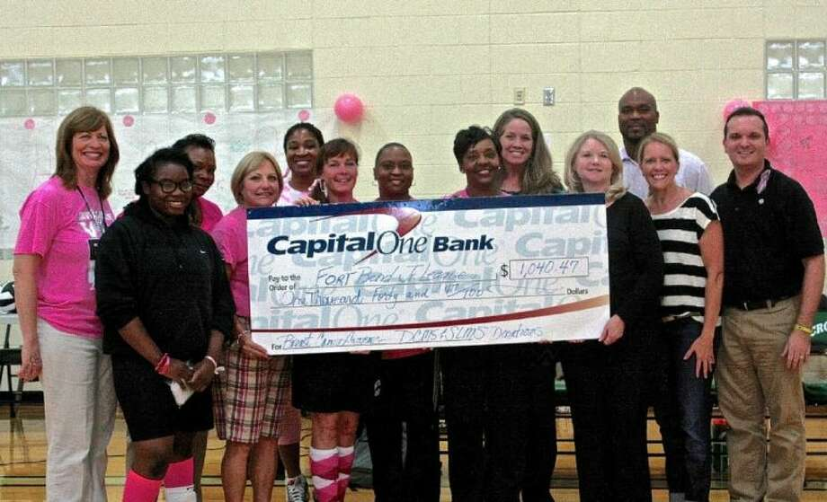 "Shown during the ""Volley Pink Project"" check presentation are (front row, from left) Favour Alejo, SLMS Volleyball Player; Karen Efron, SLMS Volleyball Coach; Debbie Cooper, SLMS Volleyball Coach and Co-Coordinator of the ""Volley Pink Project""; Versie Turner, DCMS Volleyball Coach; Stephanie Carter, DCMS Volleyball Coach; Cindy Dempster, FBJSL President; Debbie Buckner, FBJSL President-Elect; and Joshua McLain, Co-Coordinator of the ""Volley Pink Project""; and (back row, from left) Stacey Rouze, DCMS Nurse and Volleyball Assistant; Antwanita Bonom, DCMS Volleyball Coach; Chanel Johnson, DCMS Volleyball Coach; Heather Carroll, FBJSL Director of Community Relations; and Thomas Graham, DCMS Principal. Photo: Courtesy FBISD"