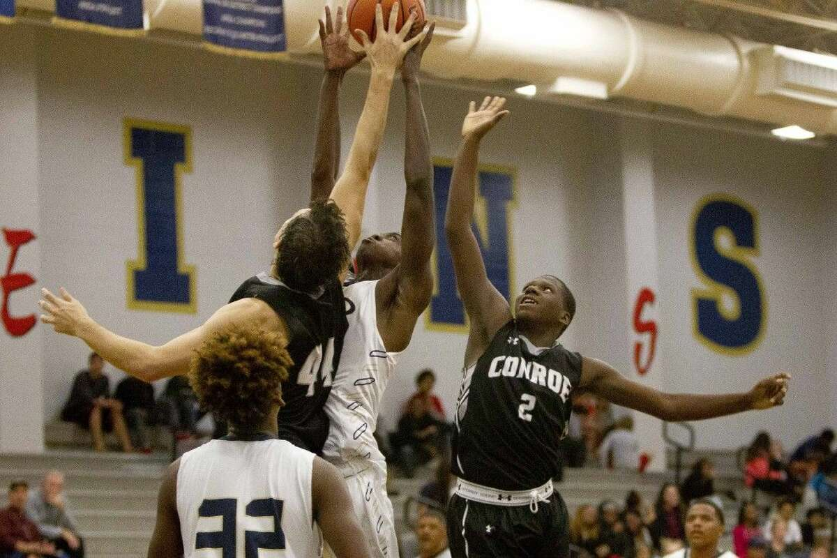 Conroe's Joshua Berry and Bryce Harris fight for a rebound during a high school basketball game Tuesday in Spring.