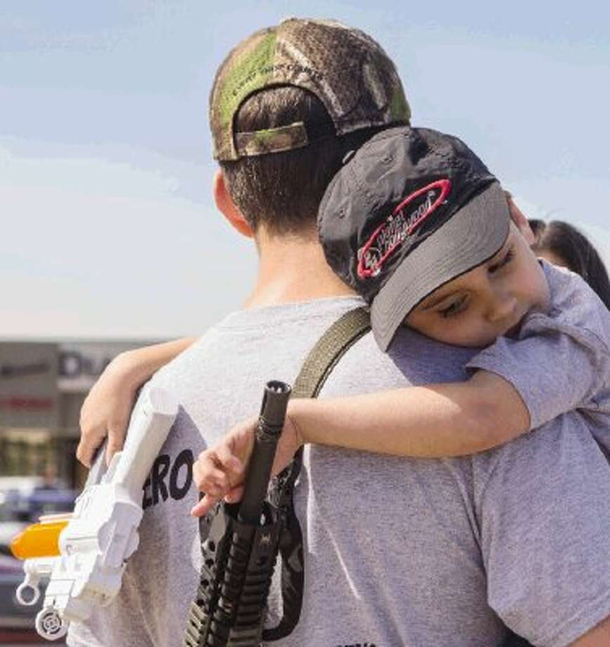 """Ralph Goff, of Kingwood, holds his son, Logan, who grasps a toy gun in one hand and grips his father's long gun with the other during Saturday's """"Open Carry"""" Walk at high noon on a short stretch of Conroe streets. Some 20 gun rights advocates walked across the North Loop 336 West overpass legally toting their long guns and a few signs in support of legalizing """"Open Carry"""" of handguns for law-abiding citizens throughout Texas. To view or purchase this photo and others like it, visit HCNpics.com. / The Conroe Courier/ The Woodland"""