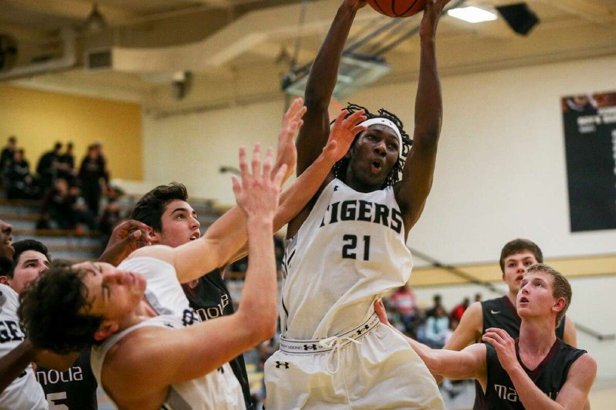 Conroe's Tremont Moore (21) rebounds the ball during the high school boys basketball game against Magnolia on Tuesday, Nov. 24, 2015, at Conroe High School. To view more photos from the game, go to HCNPics.com.