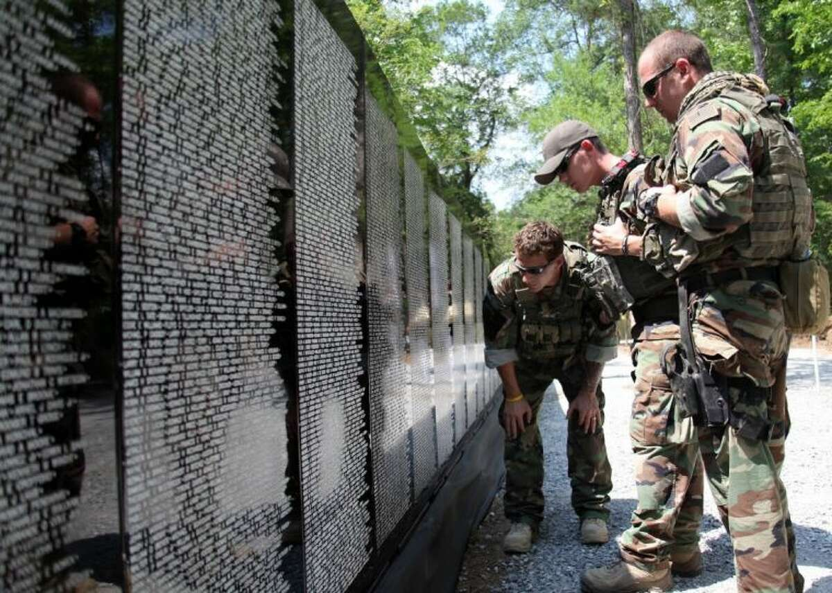 Special warfare combatant-craft crewmen assigned to Special Boat Team (SBT) 22, the only command in the Department of Defense specifically designated to conduct special operations in riverine environments, read names on the Vietnam Traveling Memorial Wall. The Wall will be in Magnolia Nov. 8-11 on the First Baptist Church grounds on FM 1488.