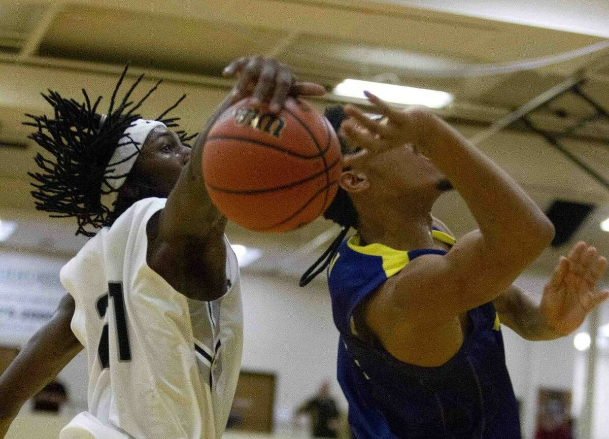 Conroe's Tremont Moore blocks a shot by Jersey Village's Layton Banks during a high school basketball game Wednesday in Conroe.