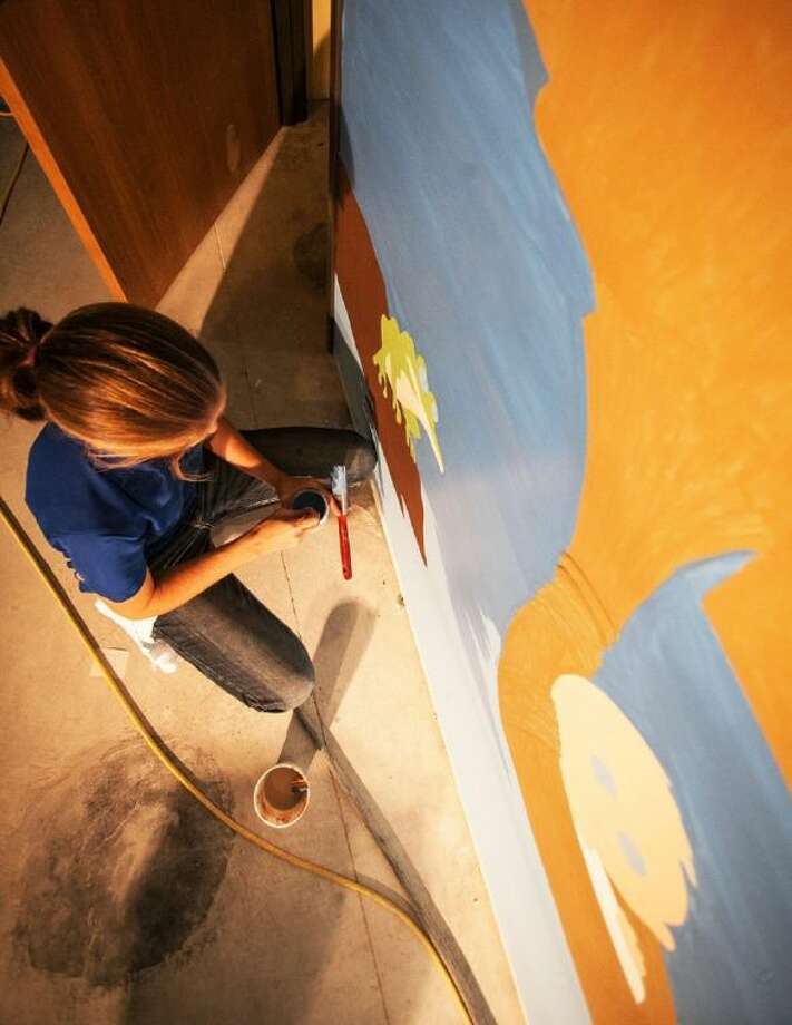 Kelli Semar works on a mural for the children's entrance of Liberty Church's new facility on FM 2025 at US 59.