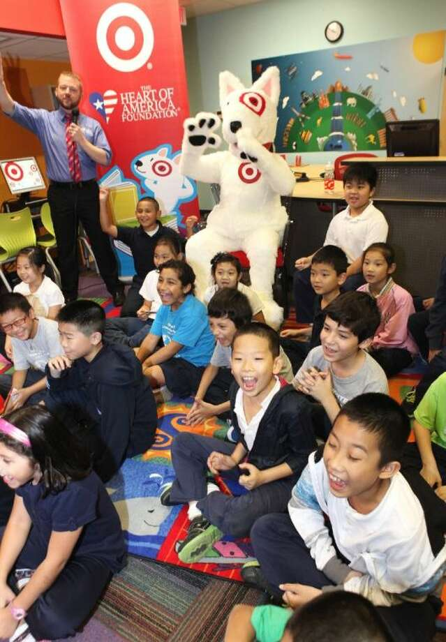 Donnie Kenneth with Heart of American Foundation and Target mascot Bullseye lead White Elementary students in a cheer after unveiling a newly renovated library for the Sharpstown-area school.
