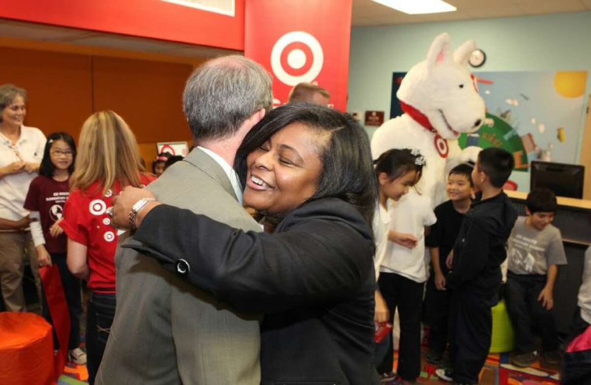 Principal Paulette Caston Bailey shares a hug with Houston ISD Trustee Greg Meyers at the unveiling of her school's newly renovated library. The library makeover is one of 25 done this year by Target Corp. and the Heart of America Foundation.