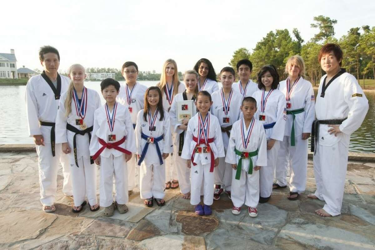 Local athletes who medaled at the 2012 USA Taekwondo Championships in July pose with their medals. Their trainers are Master Kim (far left) and Master Seo (far right).