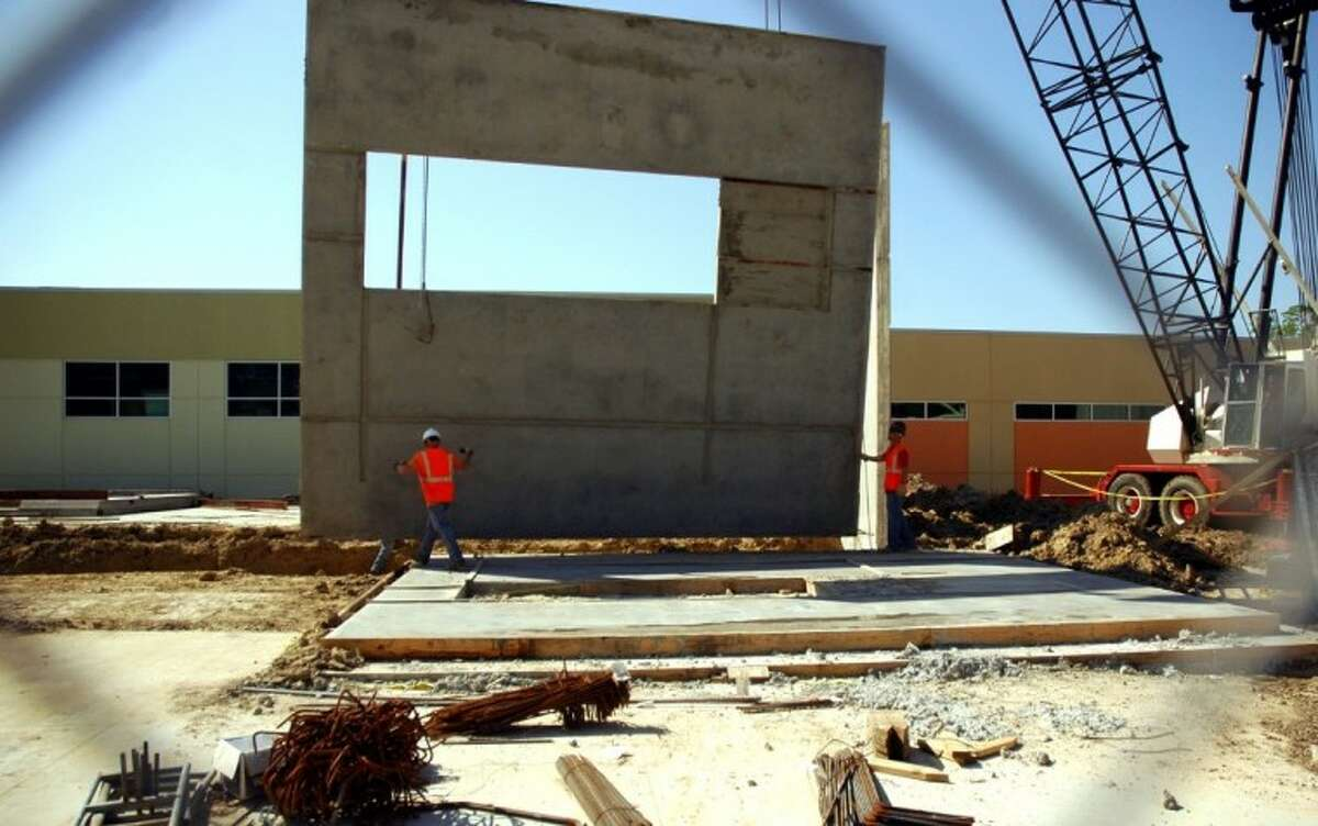 A worker guides a wall into place, viewed through a chainlink fence.