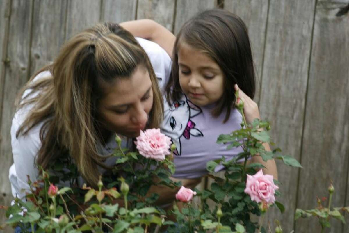 Rebecca and Audrey Gober take a moment to smell the roses at their new home in Humble Oct. 22, 2013.