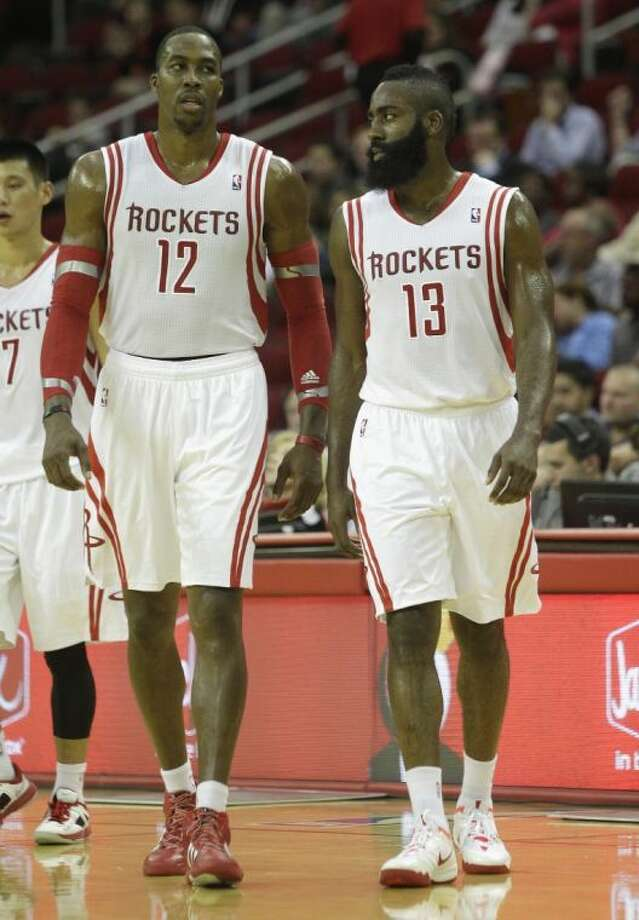 Houston Rockets center Dwight Howard (12) and guard James Harden (13) walk onto the court during a preseason game against the Dallas Mavericks on Monday in Houston. The Rockets won 100-95.