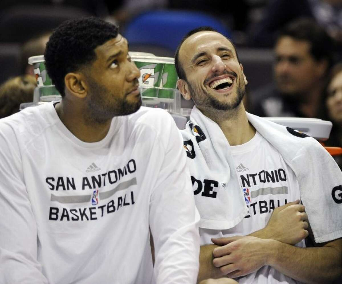 San Antonio Spurs guard Manu Ginobili, right, laughs with teammate Tim Duncan on the bench during the second half of a preseason game against the Phoenix Suns on Oct. 13 in San Antonio. Phoenix won 106-99.