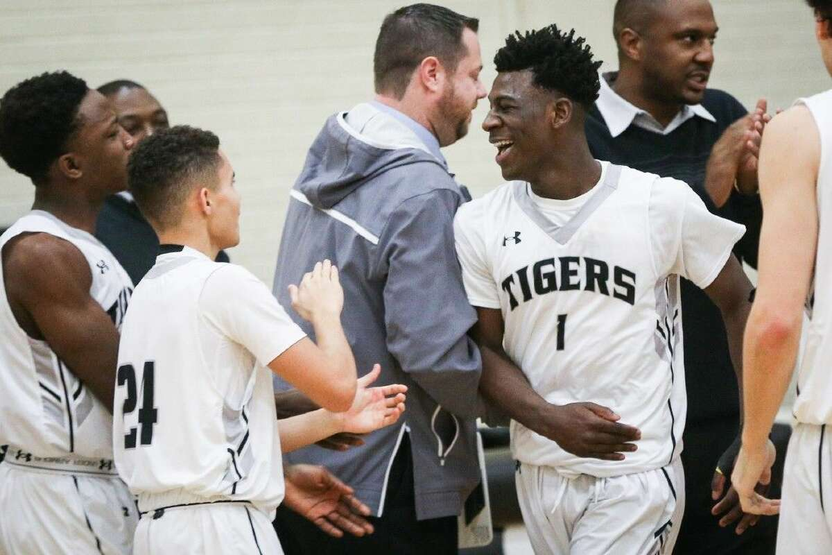 Conroe's Jay Lewis (1) celebrates with teammates during the high school boys basketball game against Klein Oak on Saturday, Dec. 19, 2015, at Conroe High School. To view more photos from the game, go to HCNPics.com.
