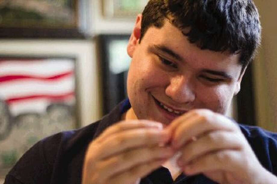 Grant Manier, an eco-friendly artist living with autism, makes collaged images from puzzle pieces, wrapping paper, magazines and other reused items in Spring Tuesday afternoon. Go to HCNPics.com to view and purchase this photo and others like it. / The Conroe Courier/ The Woodlands Villager/ The Spring Observer