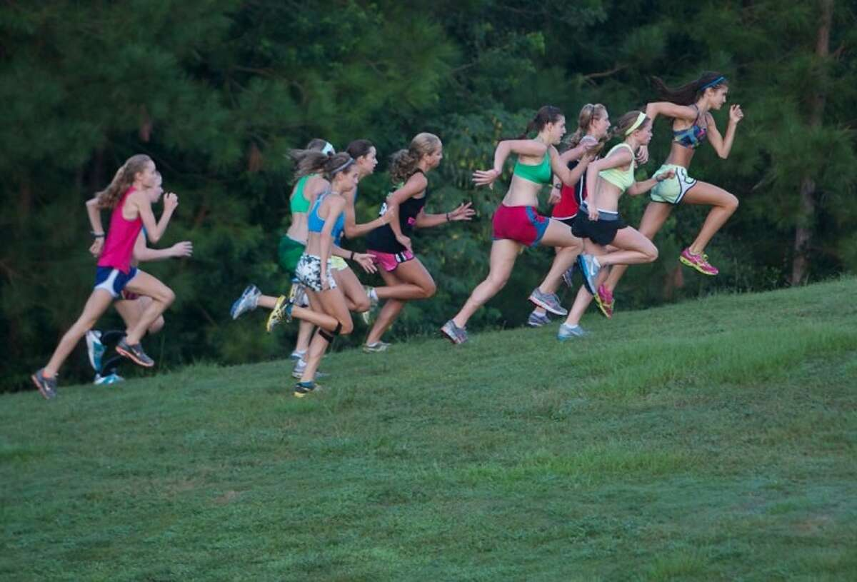 The Woodlands High School girls cross country team members charge up a hill as they make their way through Terramont Park during an early morning practice session in The Woodlands.