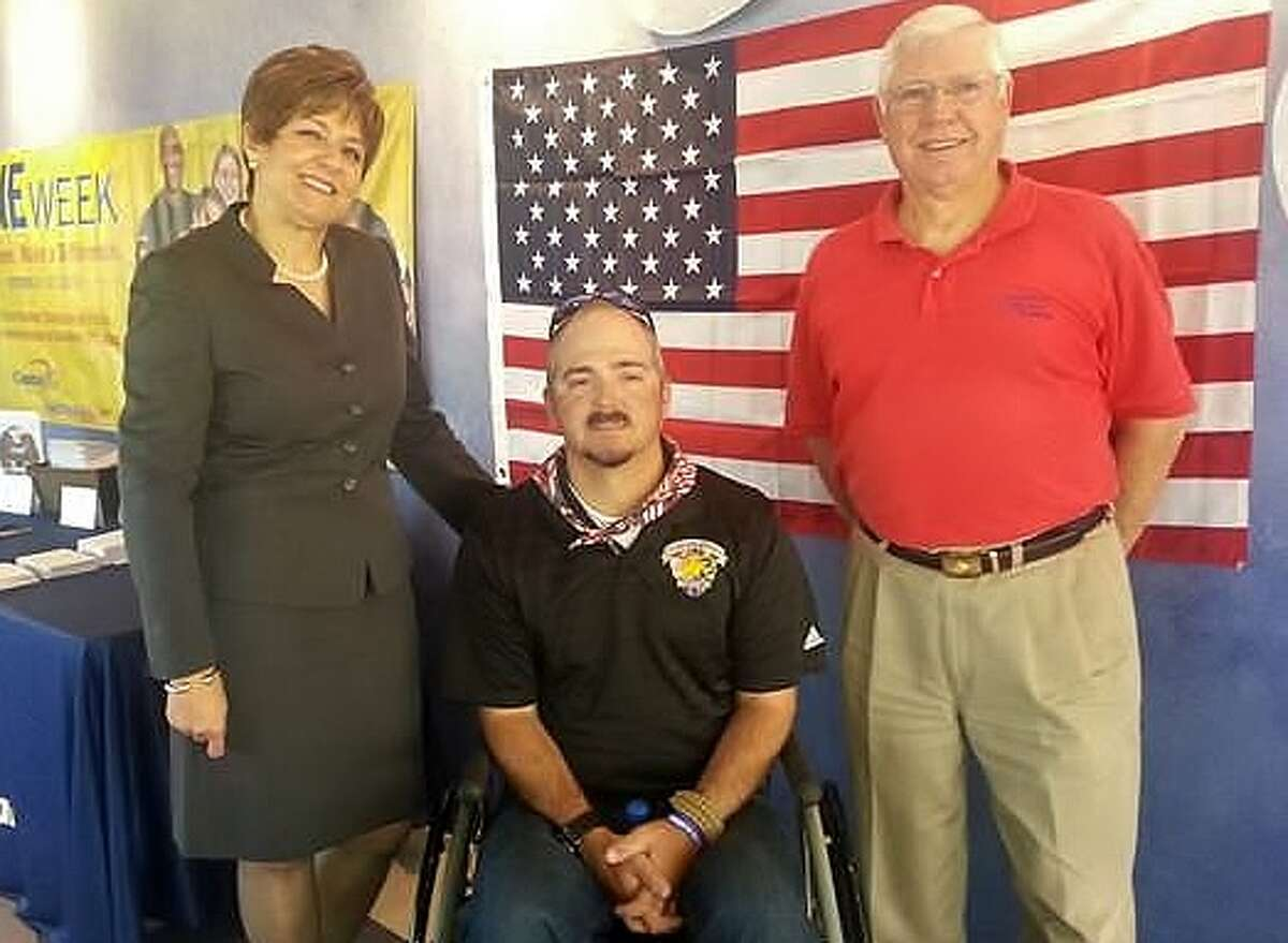 Pictured are Ray Coffey, a marine from Cypress, Texas wounded three times while serving in Iraq (center); Jerry Reed, Director of Operation Military Embrace (right) and Annella Metoyer, Capital One Bank Houston Market