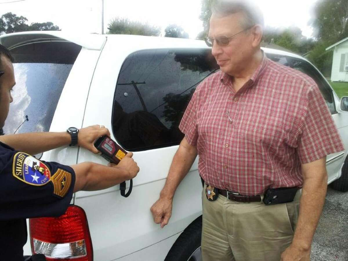 Liberty County Sheriff Bobby Rader watches a deputy demonstrate how a contraband detection device will aid the department in the discovery of illegal drugs that are stored in hidden compartments of vehicles. The device was paid for by illegal drug monies that previously were confiscated by the sheriff's office.