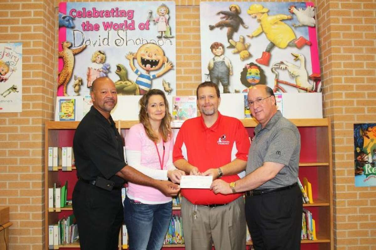 McDonald's restaurant in Cleveland recently showed its support for Southside Primary by letting Southside staff take part in McTeachers Night, earning $947.09 for the school. Pictured left to right are Roger Randolph, supervisor at the Cleveland McDonald's, Christina Purkerson, Preston Wenz and Lou Britt, the owner of the Cleveland McDonald's. Not pictured is McDonald's Manager Sheri Foster.