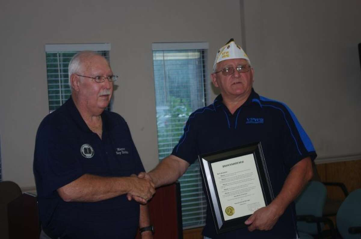 Roman Forest Mayor Ray Ricks (left) presents American Legion member John Stevens with a plaque proclaiming that the community will give special recognition to members of the American Legion and Veterans of Foreign Wars posts on Nov. 11.