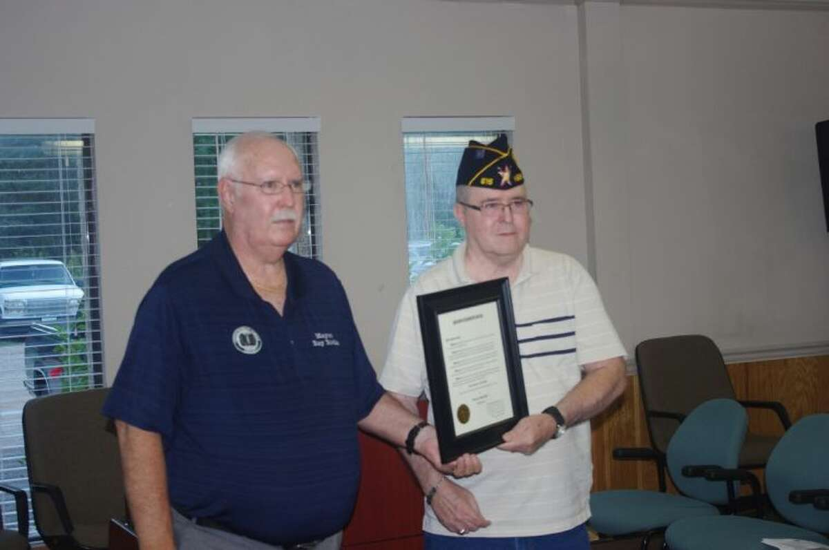 A plaque is presented to VFW member Mike Stoutenger at the Roman Forest City Council meeting on Oct. 8. Mayor Ray Ricks (left) proclaimed that local veterans will receive special local honors on Nov. 11, which is Veterans Day.