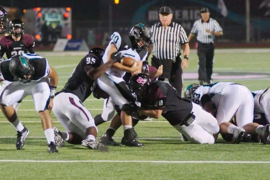 Pasadena Memorial's Isaac Mexicano (30) is sandwiched between Pearland's Avery Jordan (95) and Kevin Harvey (99) Friday at The Rig. Pearland allowed just 50 yards in a 52-6 win.