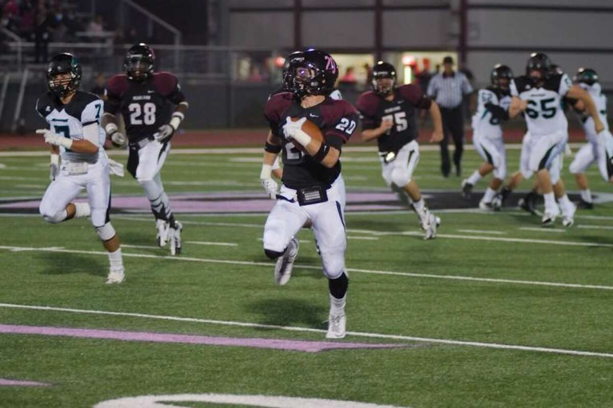 Pearland's Conner Chidester (20) breaks into the open field Friday night against Pasadena Memorial.