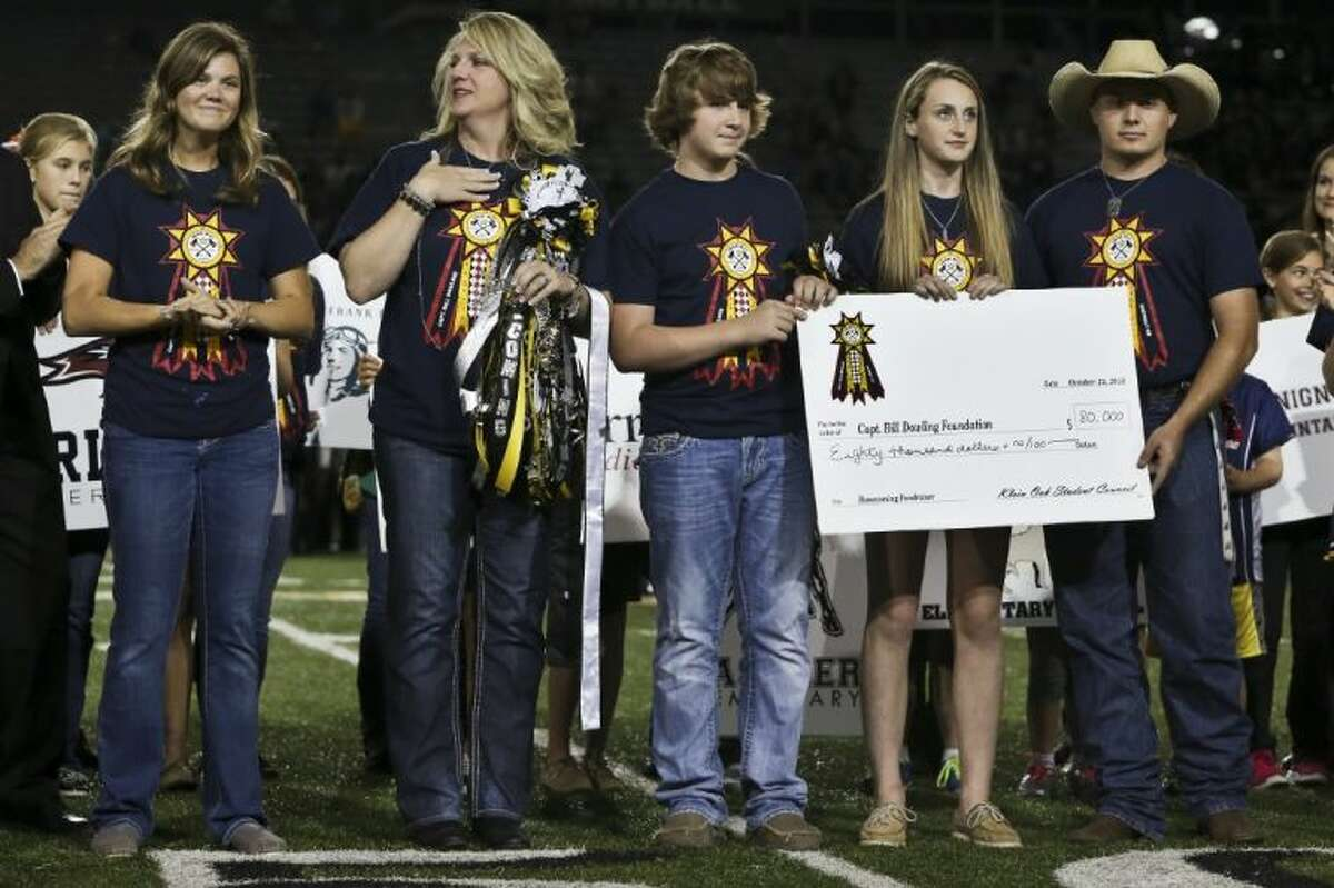 The Klein Oak Student Council presents the Dowling family a $80,000 check to support William Dowling, a Houston Fire Department firefighter who was injured in a hotel fire, during the Klein Oak homecoming halftime on Friday at Klein Memorial Stadium. To view more photos, go to HCNPics.com.