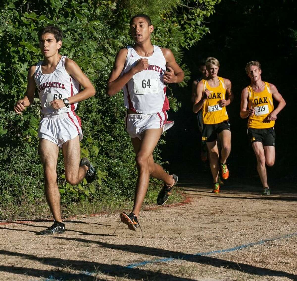 Atascocita's Josh Lozano and Andres Espinosa try to separate from the pack in the District 13-5A cross country championships at Atascocita High School on Wednesday.
