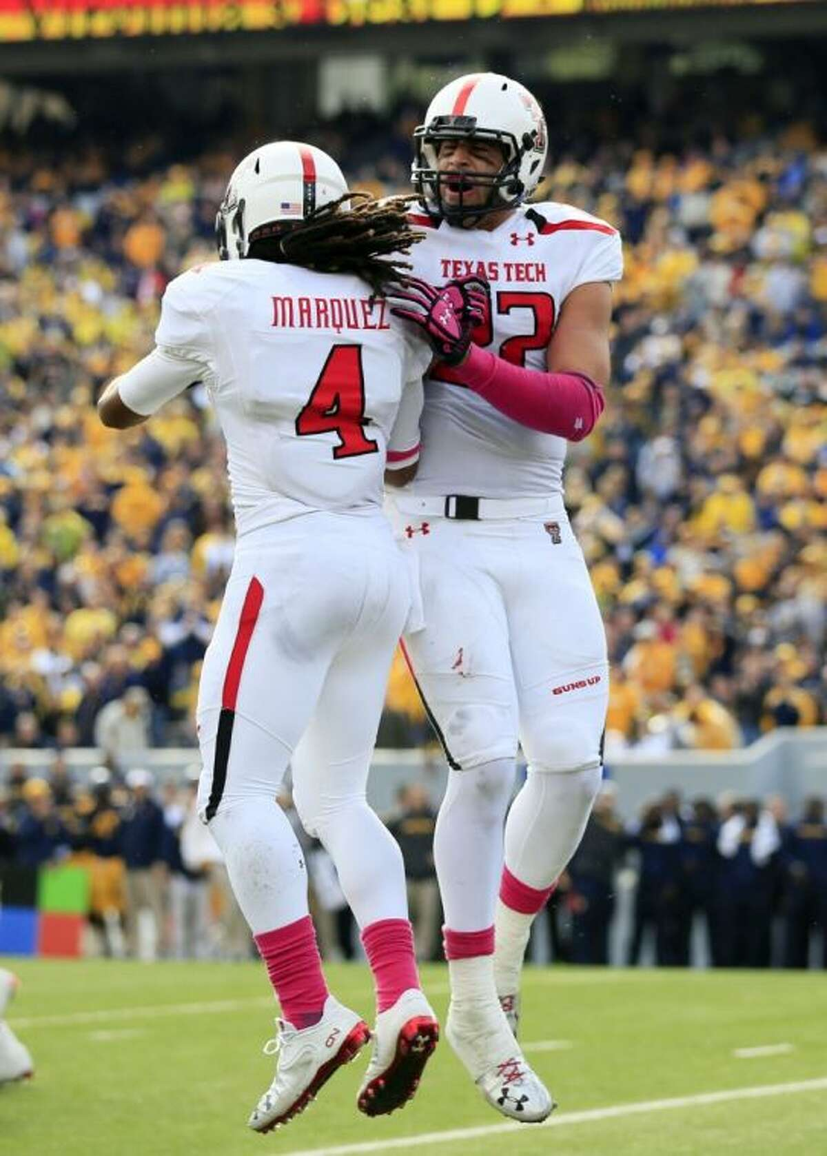 Texas Tech's Jace Amaro and Bradley Marquez (4) celebrate a touchdown during the third quarter against West Virginia on Saturday in Morgantown, W.Va. Texas Tech won 37-27.