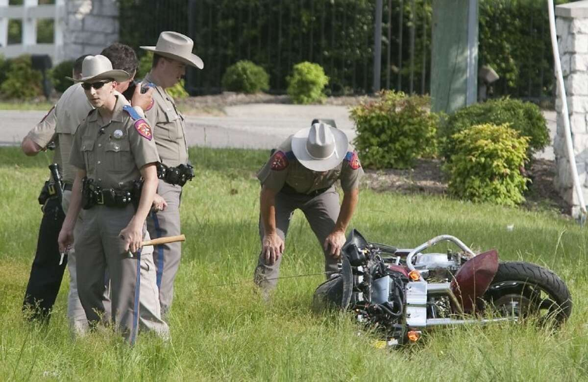 Texas Department of Public Safety Troopers investigate the scene of a fatal motorcycle accident along FM 149 near Majestic Oaks in Magnolia on Sunday.