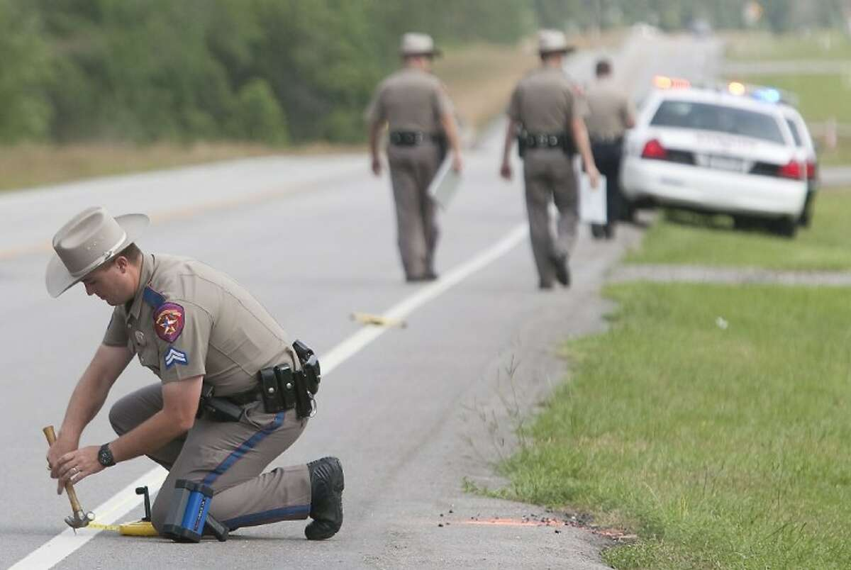A Texas Department of Public Safety Trooper collects measurements at the scene of a fatal motorcycle accident along FM 149 near Majestic Oaks in Magnolia on Sunday.