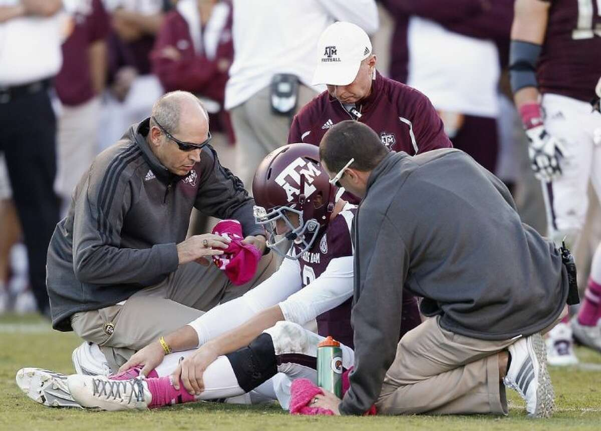 Texas A&M trainers attend to quarterback Johnny Manziel in the fourth quarter against Auburn on Saturday in College Station. Auburn won 45-41.