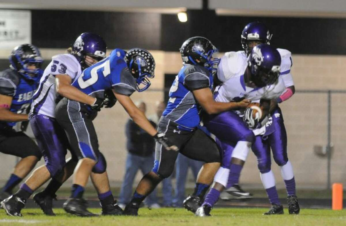 A host of New Caney Defenders push Humble's Tyler Osborn back on Friday at Don Ford Stadium.