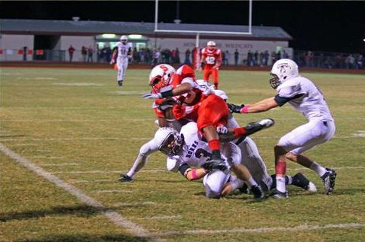Longhorn defenders Craig O'Farrell, Hunter Johnson (1), and Tristan Williamson contain and bring down the Wildkats' Jay Bradford (23) in the annual Battle of the Bell on Friday, Oct. 25. Splendora won over Tarkington, 35-34.