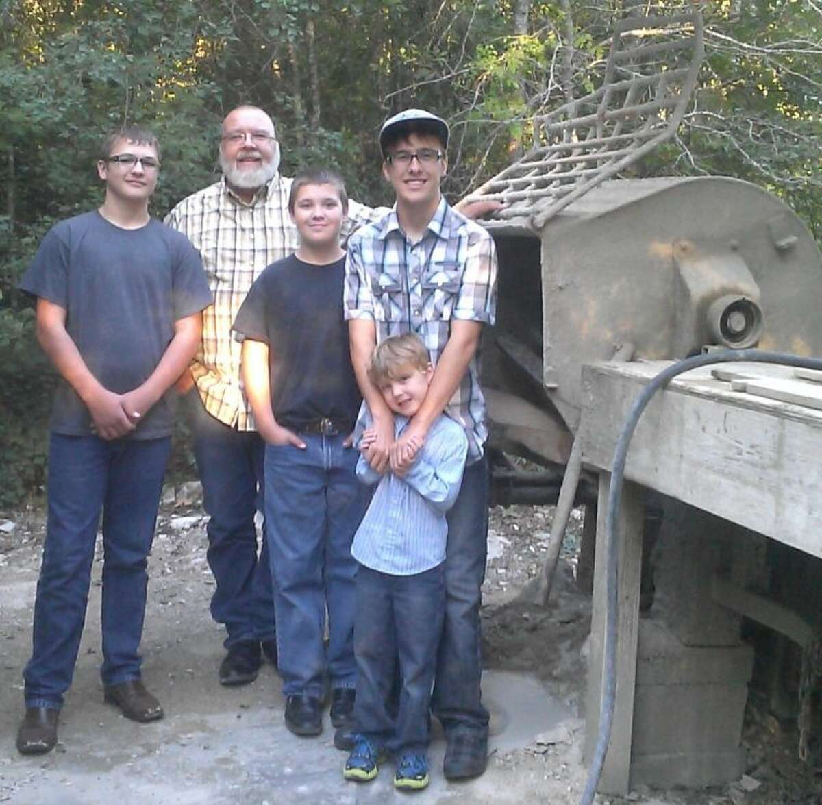 Doc, 18, Stephen, 15, Bryan, 12, and, Hunter, 5, spend many hours a week helping their dad, Nicky Sikes, mix cement used to make concrete picnic tables, fountains and bird baths for their family business.
