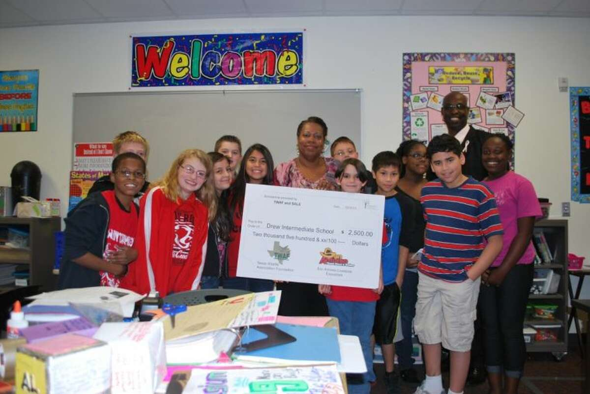 With her principal, Walter Berringer and her sixth grade science class surrounding her, Drew Intermediate School science teacher Dana Northern proudly displays the $2500.00 grant award check from the Texas Wildlife Association Federation Natural Resource-Excellence in Teaching Scholarship.