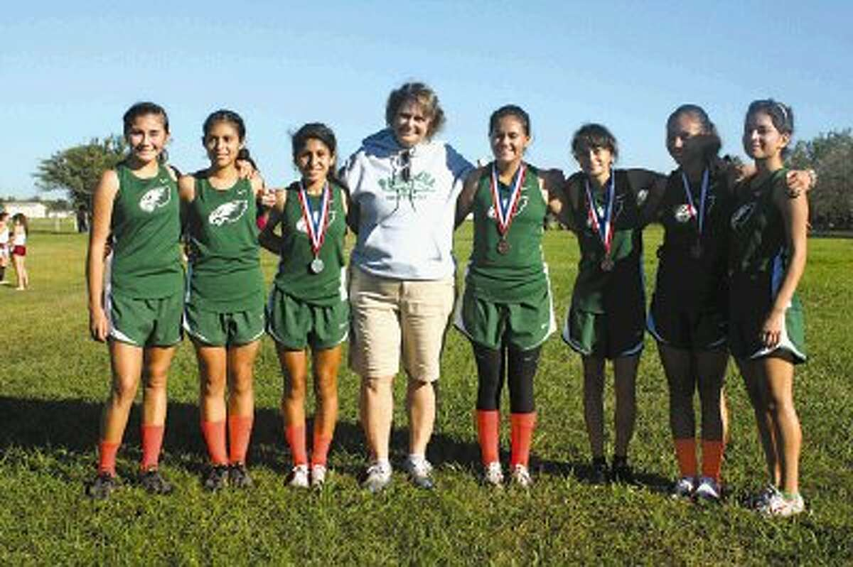 Pasadena High School girls cross country coach Denise Pearce poses with her newly-crowned District 22-5A champions after the team defeated defending champion Manvel 61-75. The Lady Eagles will be practicing this week for the Region III meet at Atascocita High School Saturday afternoon around 1 p.m.