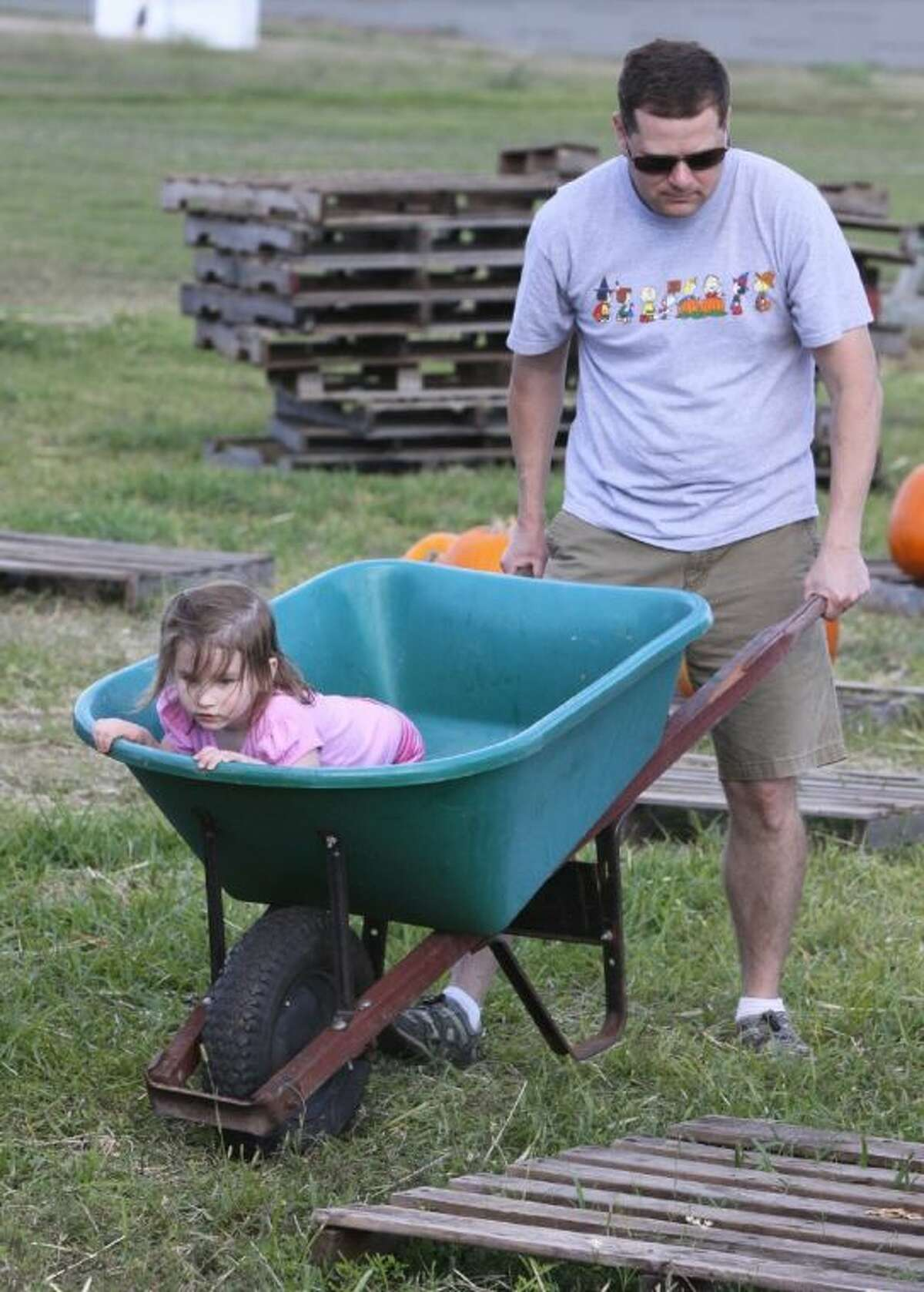 Brian White gets some help from his daughter Abby, 3, in picking out a pumpkin at the Pumpkin Patch at Holy Cross Episcopal Church in Sugar Land on Saturday, Oct. 26.