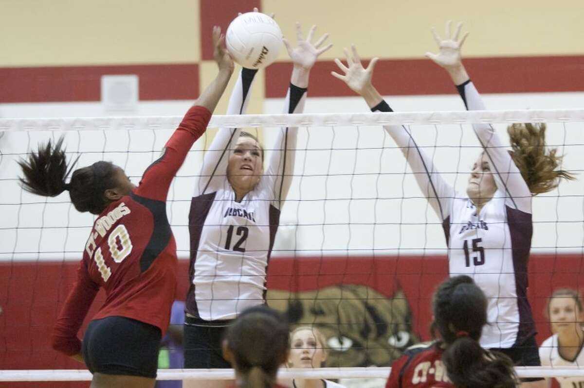 Cy-Fair's KeelyHayesandAmanda Hellergo up for a block against Cy Woods'Erica Ogwumikein the two teams' match on Tuesday at Cy Woods High School. Cy-Fair won 3-1, handing Cy Woods its first district loss in three years.