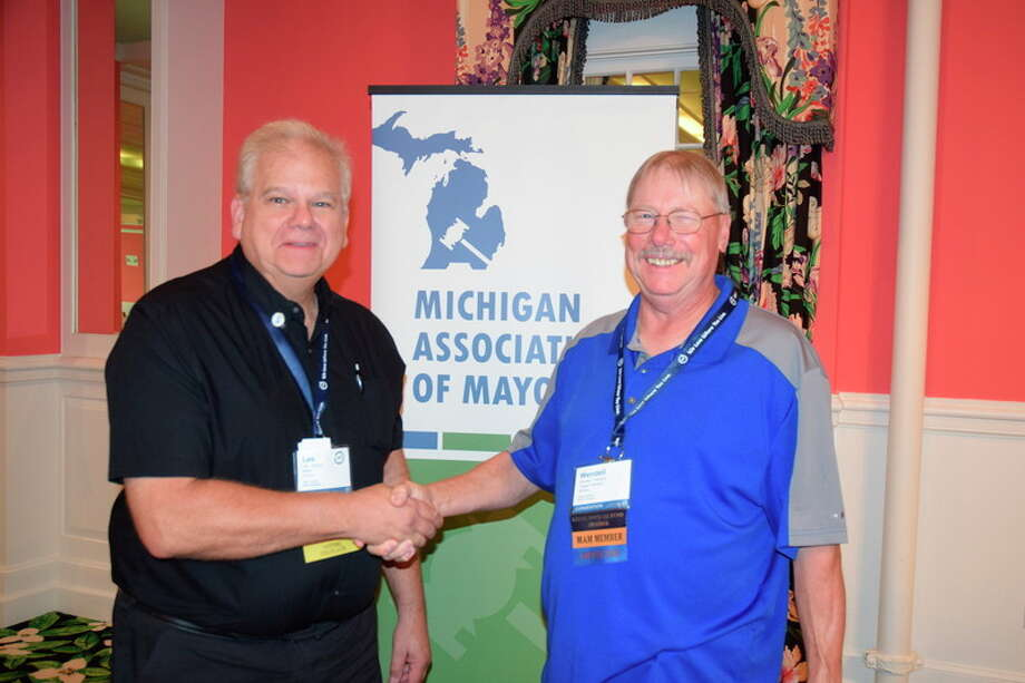 Photo provided Auburn Mayor Lee Kilbourn, left, and Baraga Village President Wendell Dompier shake hands after being elected president and vice president, respectively, of the Michigan Association of Mayors.