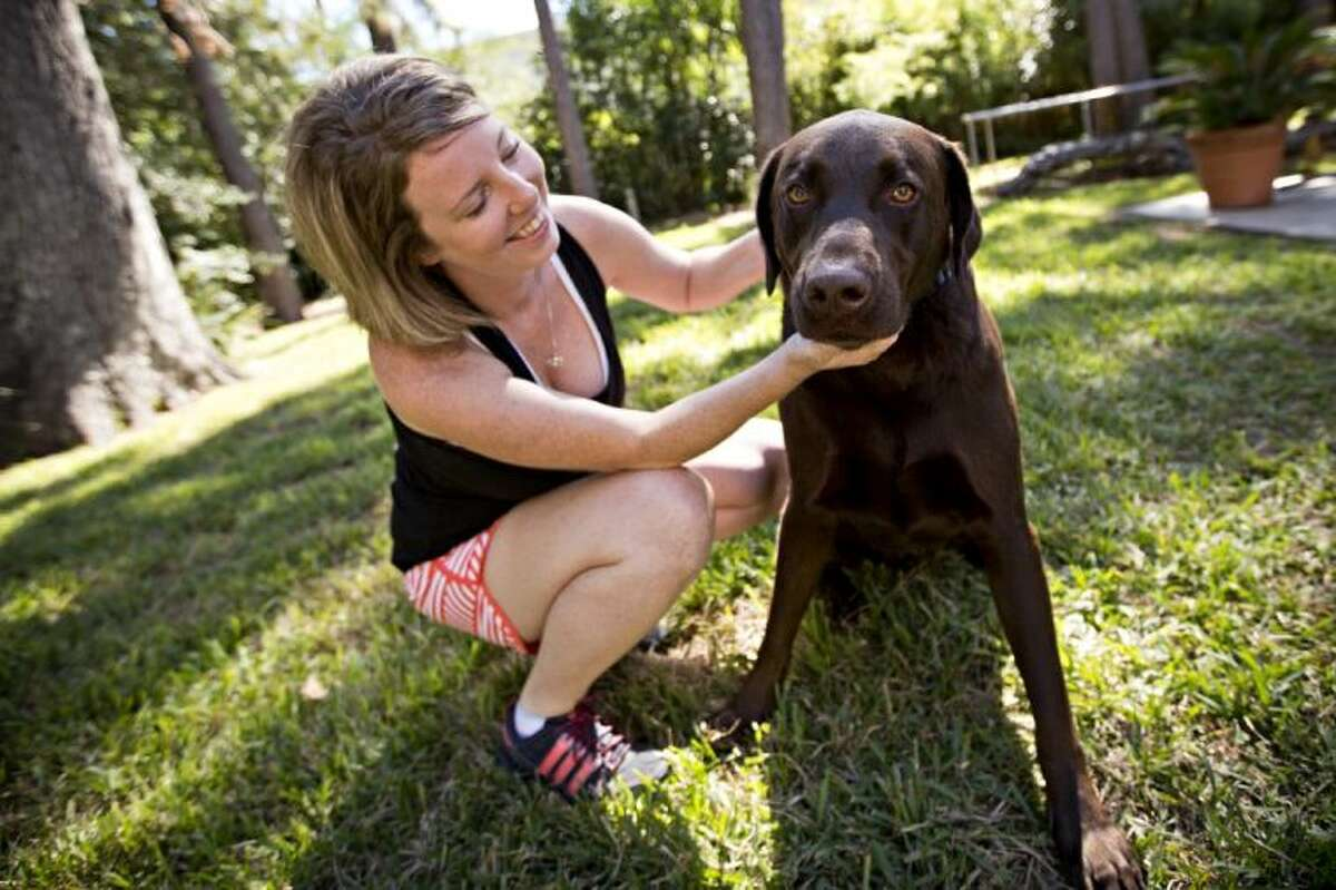 Bianca Hurd plays outside with her 3-year-old Chocolate Labrador, Duece.