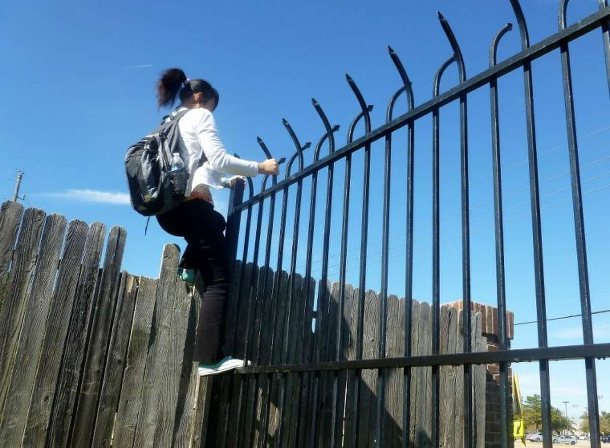 Uyen Nguyen, a senior at Klein Forest, climbs over a locked gate in the Champions Point Grove subdivision to get home.