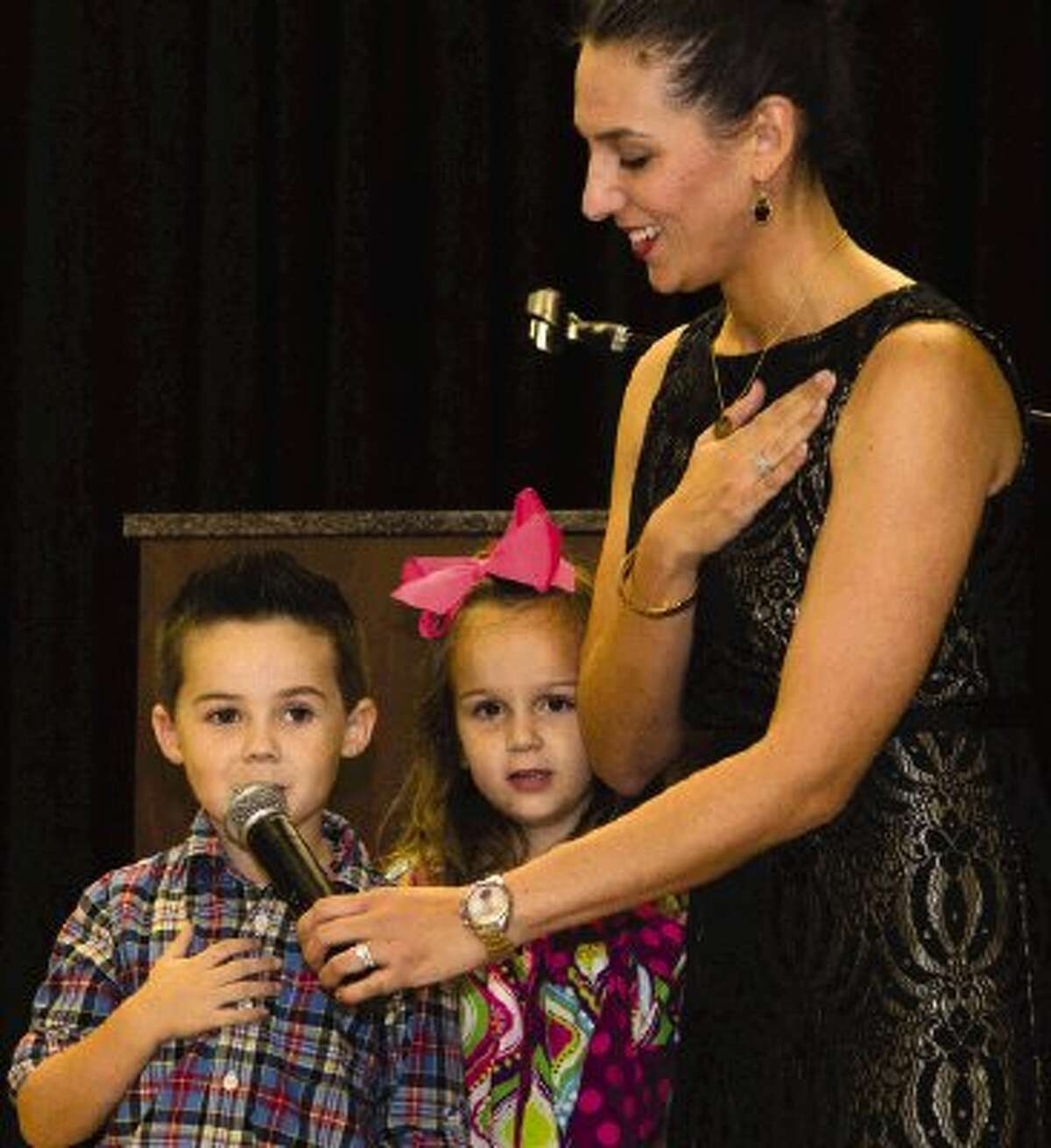 Ann K. Snyder Elementary School Principal Lindsay Ardion recites the Pledge of Allegiance with Braden Sanchez and Hayes Watson Monday night during an event to dedicate the new school to the woman it is named after. Ann K. Snyder, president and CEO of Interfaith of The Woodlands, was honored by children singing and with a video produced by her family and colleagues.