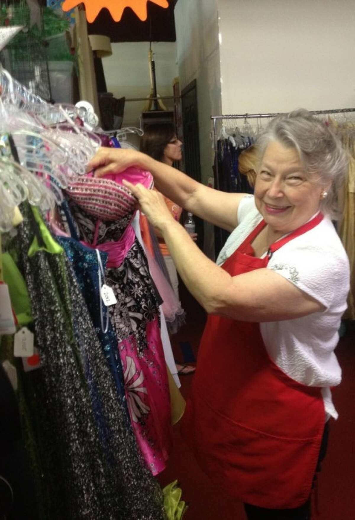 Linda Goerland organizes the prom dresses for Bay Area Cinderellas at the Assistance League Resale Shop in Webster.