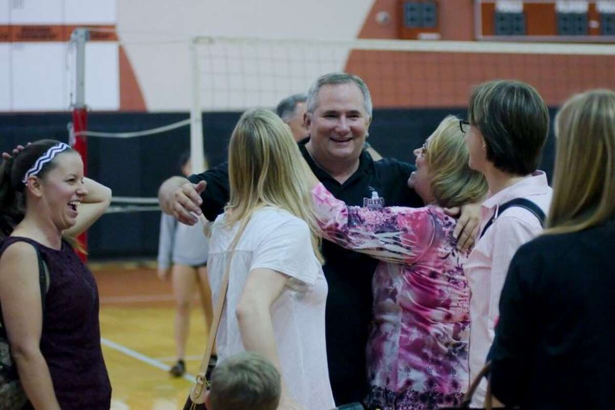 Pearland volleyball coach John Turner is congratulated on his 700th career win as he surrounded by former players and parents and receives a hug from Debra Mishla whose daughter previously played for Turner.