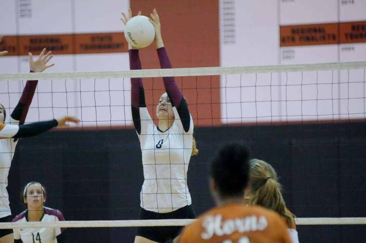 Pearland's Cassidy Nussman (8) goes high to block a shot against Pasadena Dobie Tuesday night. Pearland won in straight sets and begins the playoffs next week.
