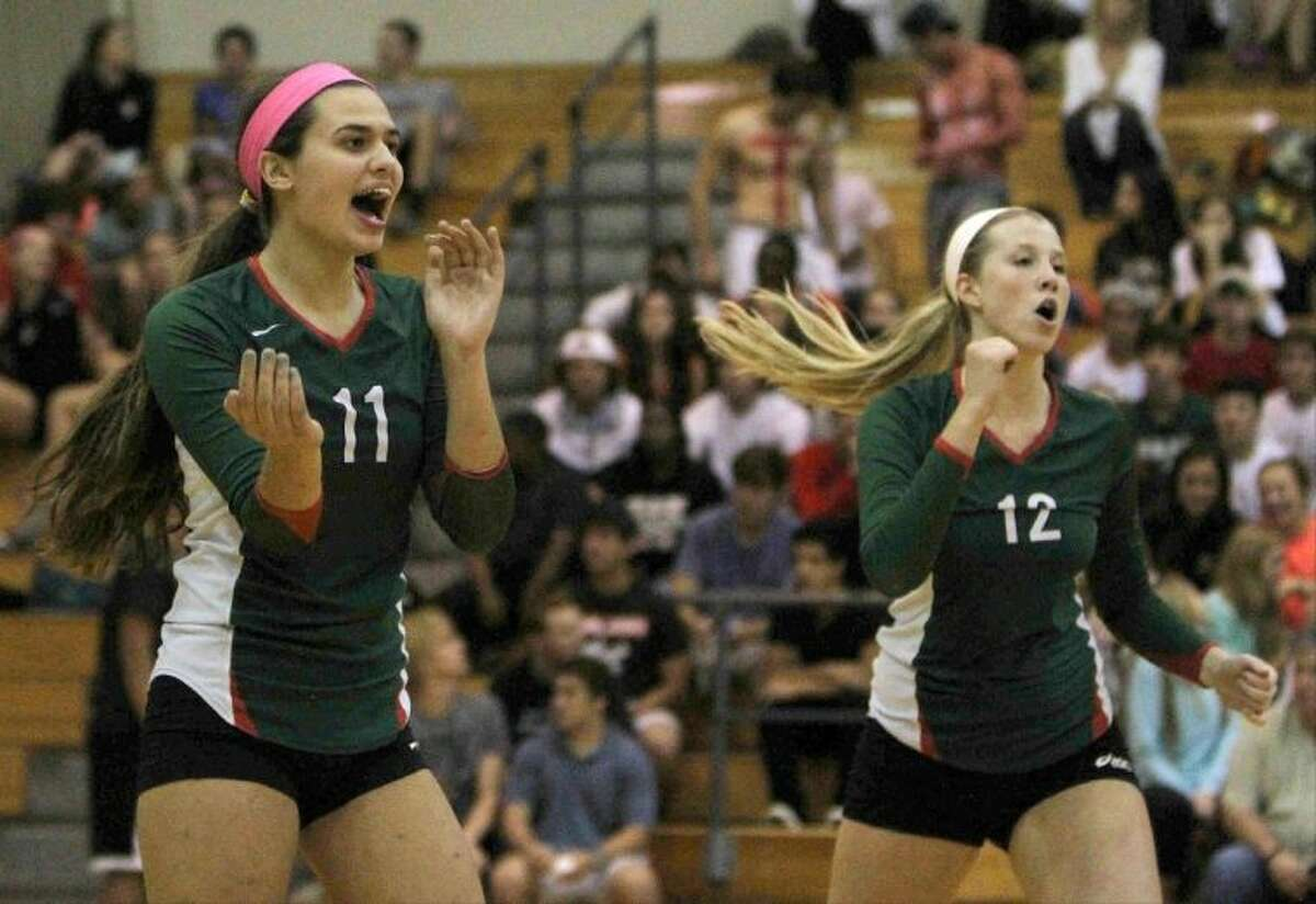 The Woodlands' Courtney Quinn (11) and Rachel Reed (12) celebrate a point during a match against Oak Ridge on Tuesday at The Woodlands High School. To view or purchase this photo and others like it, visit HCNpics.com.