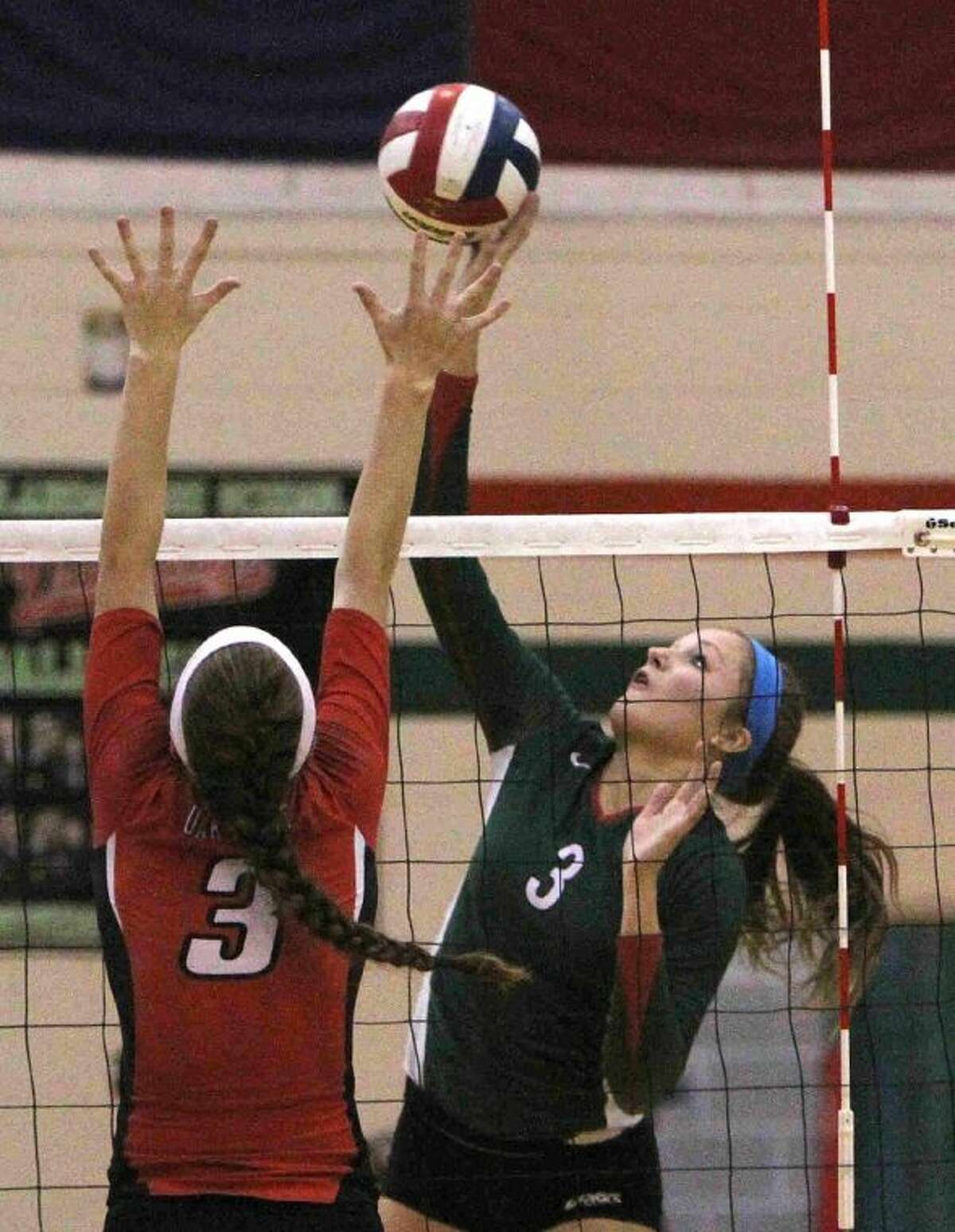 The Woodlands' Madison McDaniel spikes the ball as Oak Ridge's Jaclyn Ward goes up for a block during a match on Tuesday at The Woodlands High School. To view or purchase this photo and others like it, visit HCNpics.com.