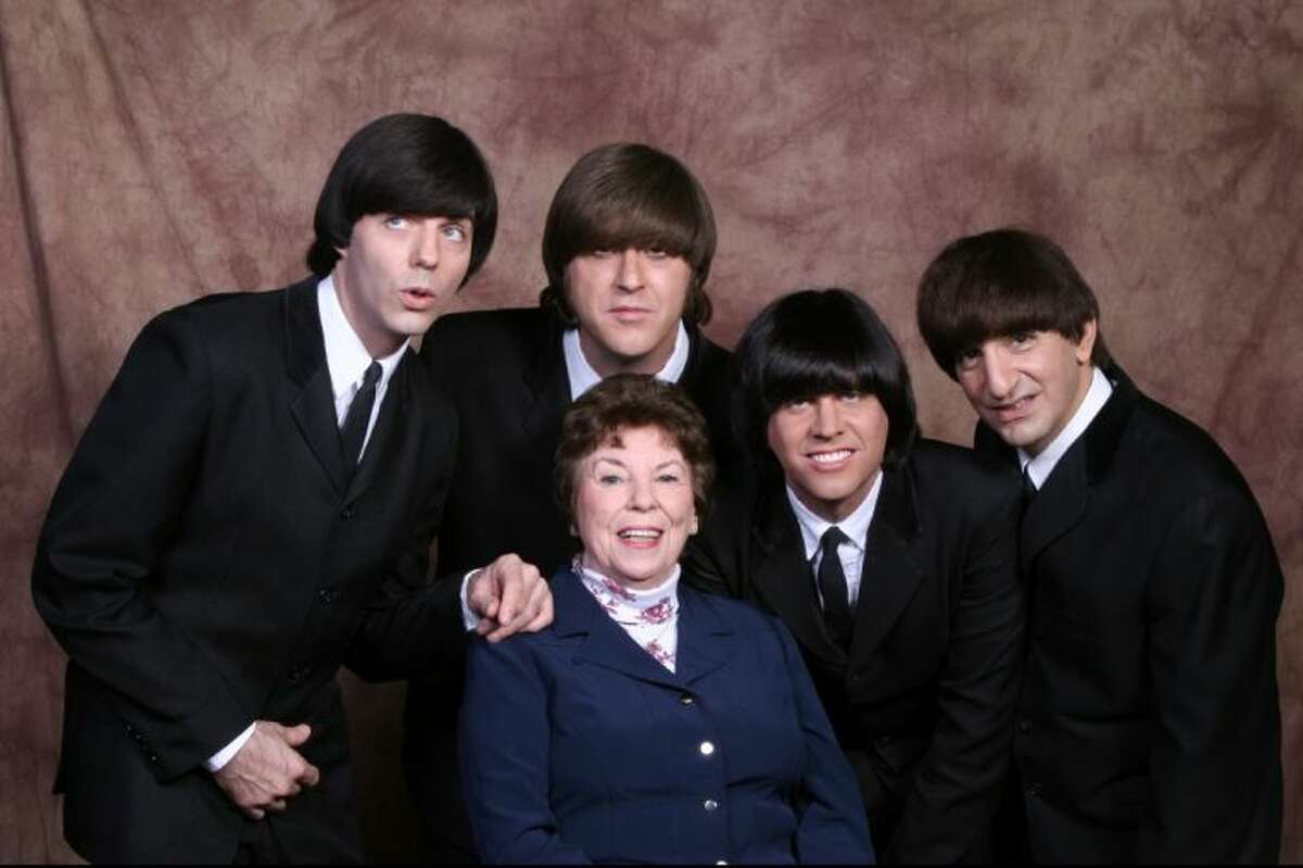 Louise Harrison, older sister of George Harrison, with the members of Beatles tribute group, Liverpool Legends.