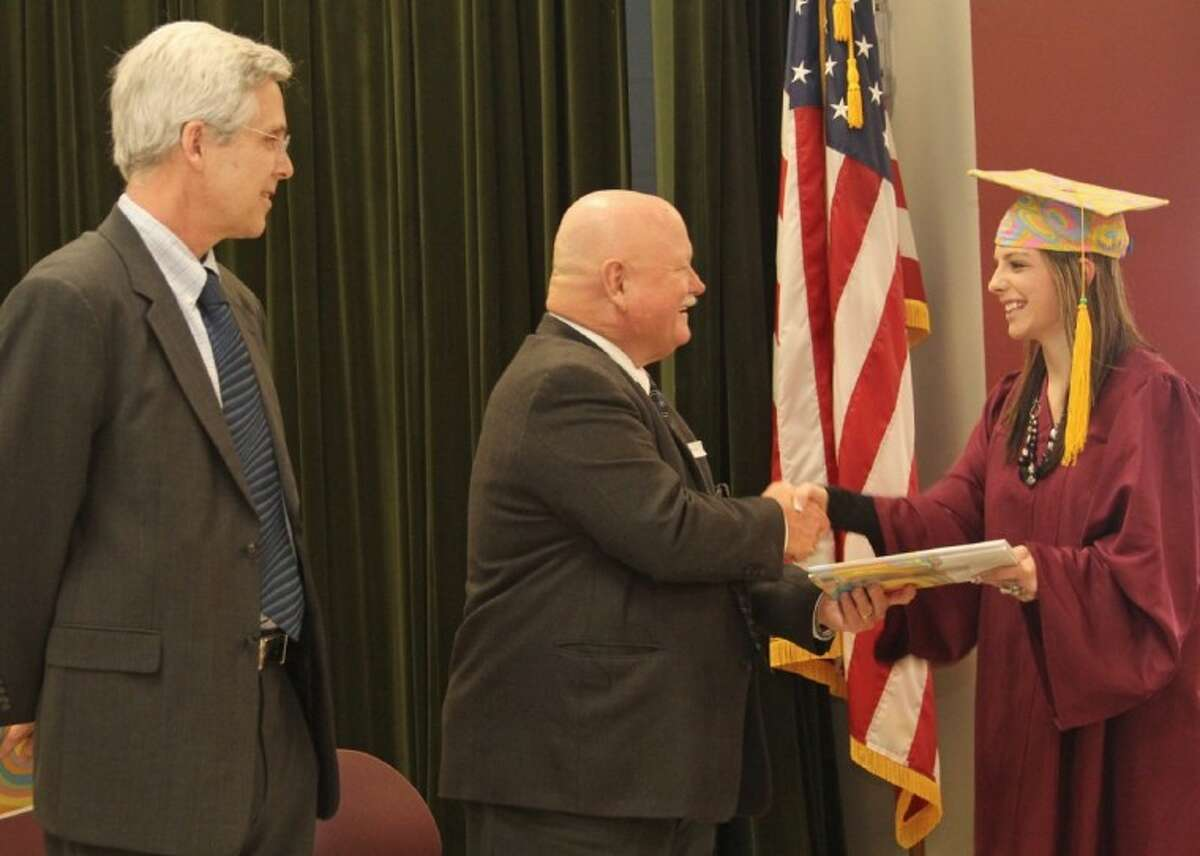 As Pearland ISD superintendent Dr. John Kelly looks on, board president Virgil Gant (middle) congratulates a PACE Center student on receiving her diploma.