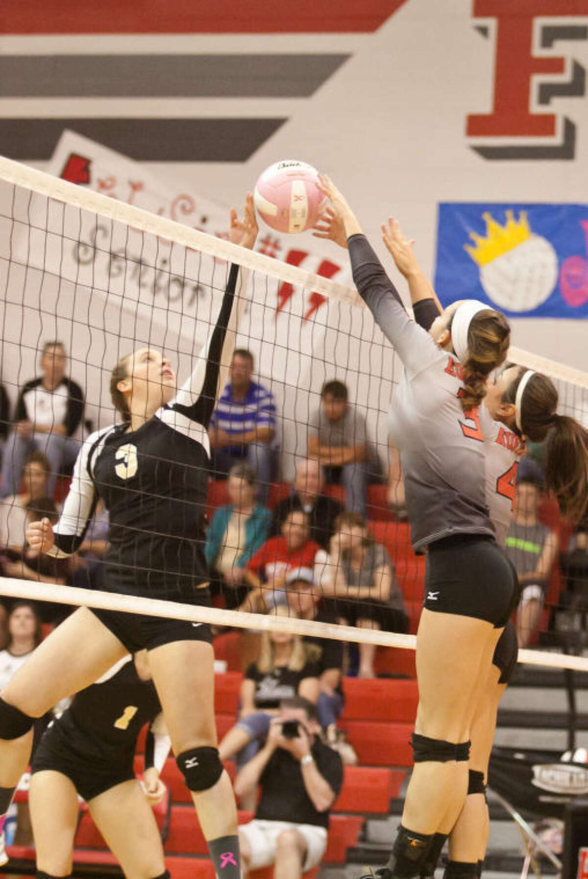 Liberty's Kaitlyn Slack (3), gets block by Huffman's Shelby Russell (3) and Bailey Sousa (4) in the first set of their match on Oct. 29, 2013. (Photo by AMANDA J. CAIN/ The Observer)